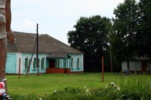 Школа в Протасово, 2009 год. На скамеечке кто-то сидит.