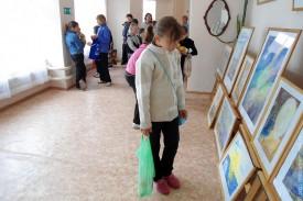 Дети рассматривают картины юных художников.