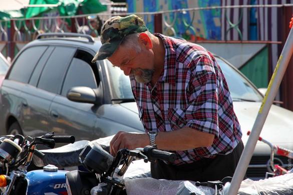 Осматривает мотоцикл.