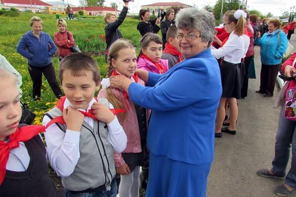 Пионерские галстуки ребятам повязывает руководитель дома детского творчества Малоархангельска Коклевская Надежда Васильевна.
