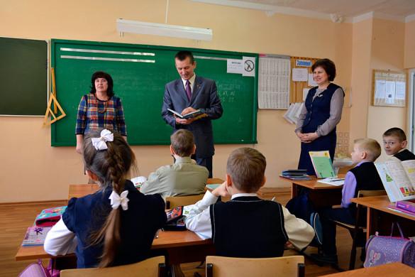 Депутат Вдовин смотрит дневник школьника МСШ №1.
