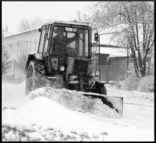 Трактор чистит снег.