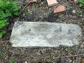 Надгробный камень лежит по правую руку от выхода, ведущего к пруду.