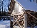 Печку отшельник топит дровами.